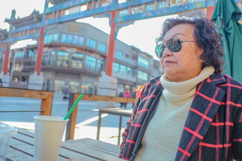 Portrait photo of Asian senior women drinking Coffe on Qianmen street The famous street in beijing. Portrait photo of Asian senior woman drinking Coffe on royalty free stock images