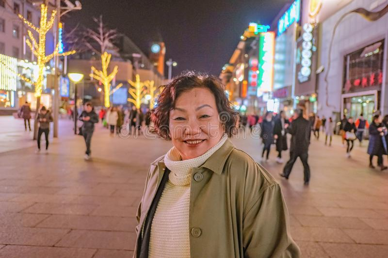 Portrait photo asian women traveler Smile and standing on wangfujing the famous walking Street in beijing royalty free stock image