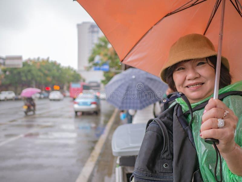 Portrait Photo of Beautiful Senior asian women Waiting Bus at Bus Stop and Holding the umbrella in Zhangjiajie City China stock photo