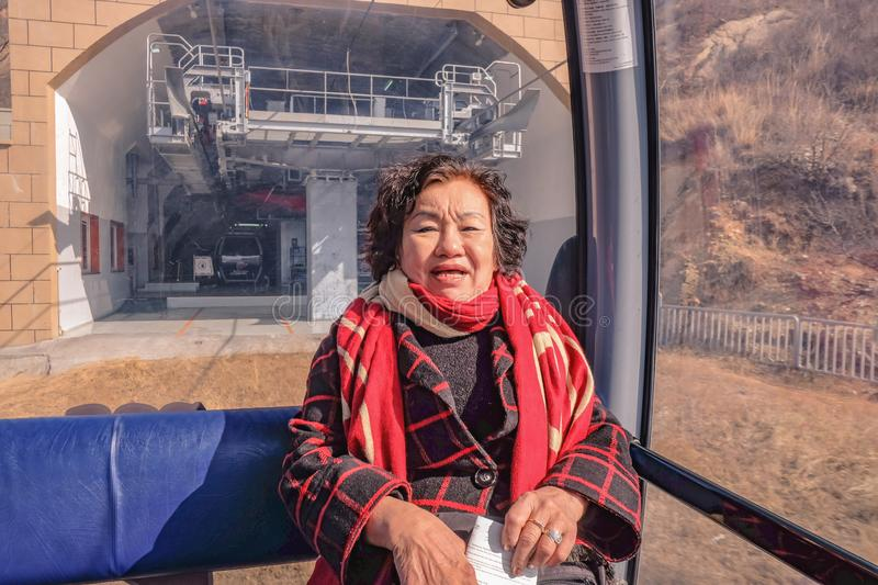 Portrait photo of Senior asian women traveler sitting on cable Car cross the mountain to the Great Wall of China at Beijing City. royalty free stock photo