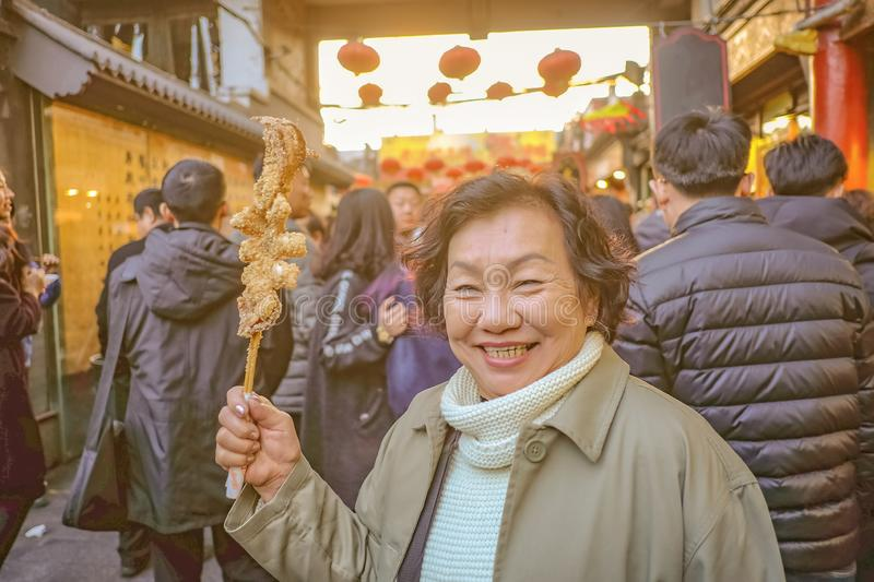 Portrait Photo of Senior asian women Hold Fried Giant Octopus in Wangfujing Walking street and street food in beijing city royalty free stock photo