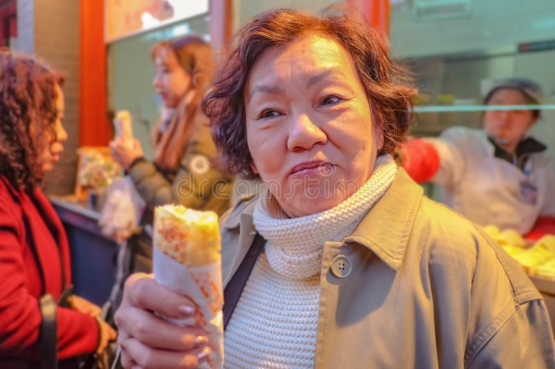 Portrait Photo of Senior asian women Holding Spring roll in Wangfujing Walking street and street food in beijing city stock photography