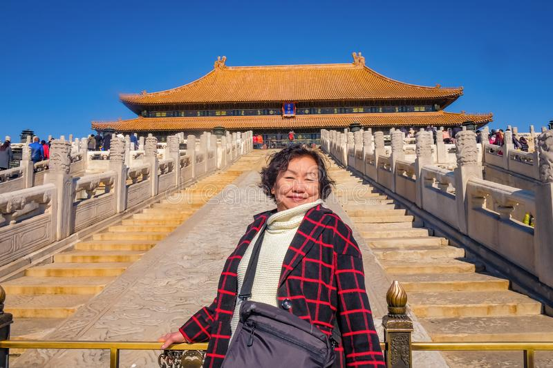 Portrait photo of Senior asian women with `Taihedian ` palace in the Forbidden Palace Gate at beijing royalty free stock photos