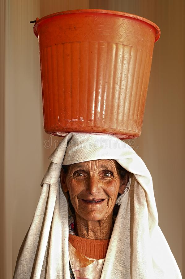 Portrait Photo of Woman Carrying Orange Plastic Pail on Head royalty free stock image