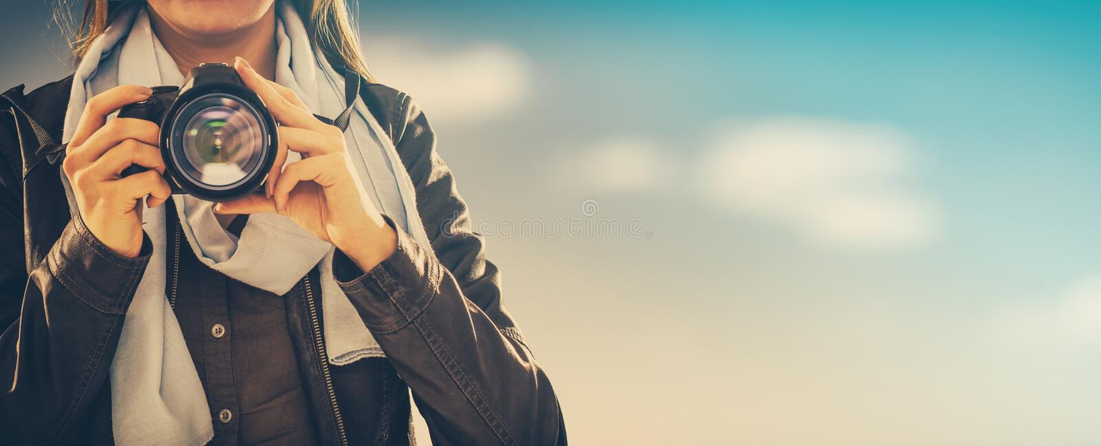 Portrait of a photographer covering her face with camera. royalty free stock image