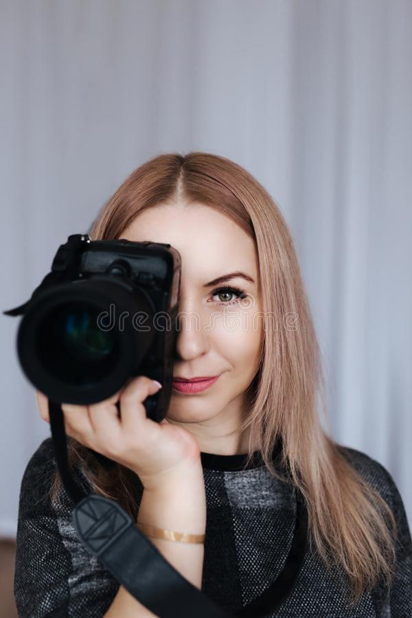 Portrait of a photographer covering her face with the camera. stock images