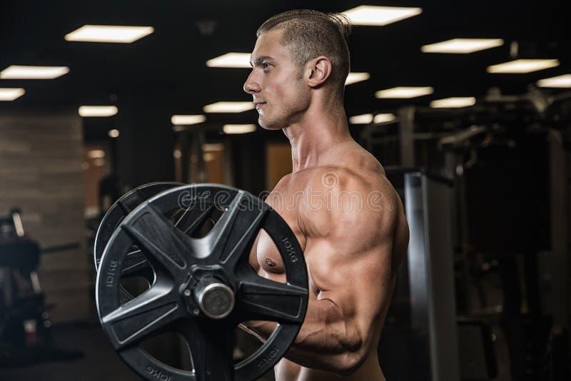 Portrait physiquement d'un jeune homme jugeant des poids disponibles photographie stock