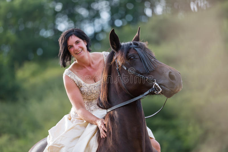Portrait of a woman with bridal dress and Andalusian horse royalty free stock images