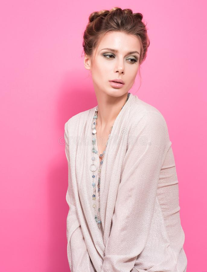 Portrait in pink colour. Beautiful young woman in a light blouse posing and holding the beads royalty free stock photo
