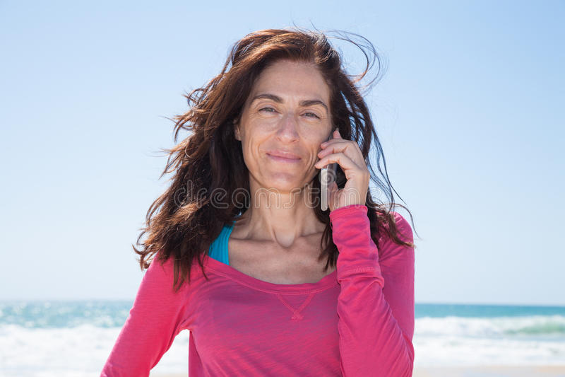 Portrait pink shirt woman talking on mobile sea behind stock photo