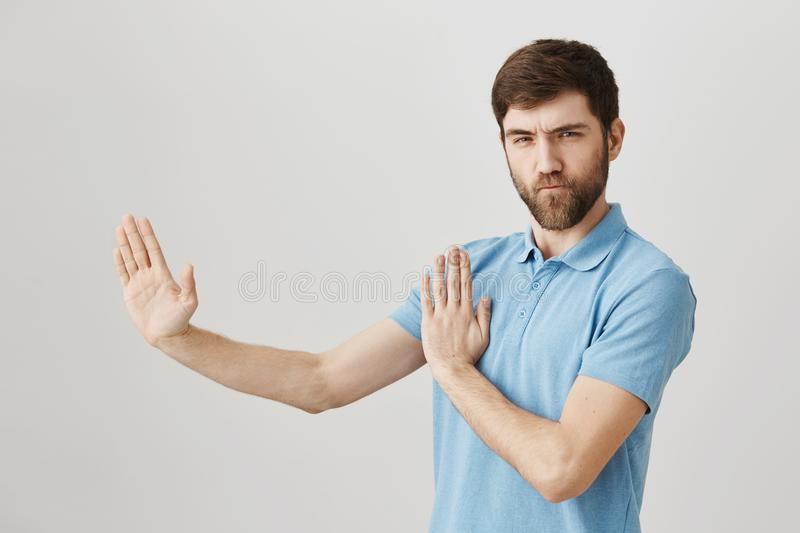 Portrait of playful charming european man who acts like ninja or karate fighter, standing half-turned in defence pose. With raised palms and looking confidently stock image