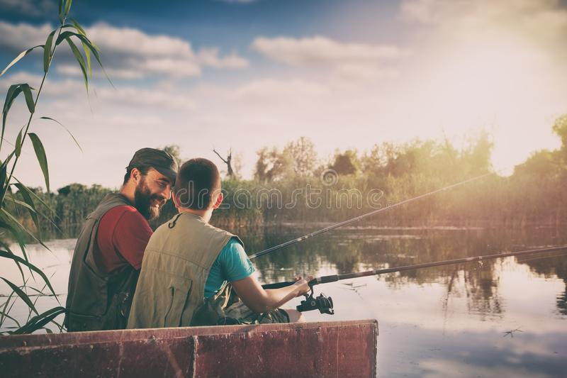 Handsome father and son sitting in boat on lake while enjoying fishing together stock photo