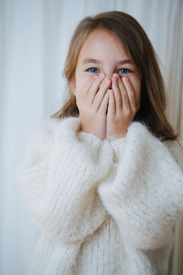 Portrait of a playful little girl in white fluffy knitted sweater covering face stock photography