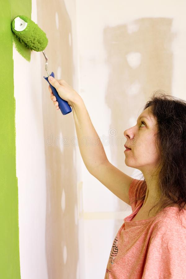 Portrait of a pretty young woman in pink t-shirt is carefully painting green interior wall with roller in a new home stock photography
