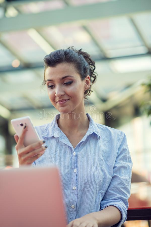 Portrait of a playful young girl taking selfie with mobile phone while sitting with laptop computer at a cafe outdoors stock photography