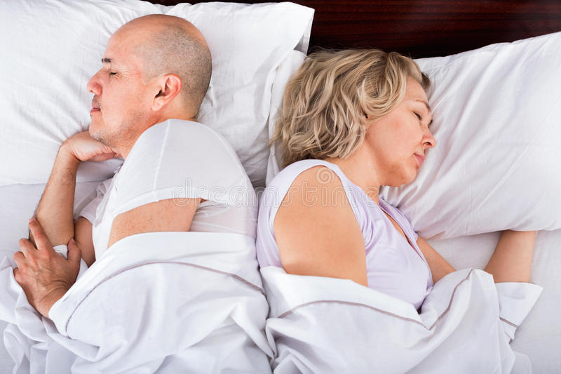 Portrait of pleasant ordinary mature couple napping in bed stock images