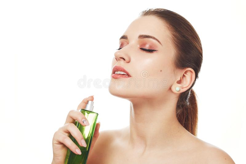 Portrait of pleased adorable woman with wonderful make up, uses her favourite parfume, looks beautifully, closes eyes with pleasur stock image