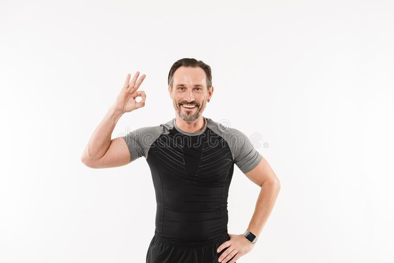 Portrait of pleased adult man fitness instructor smiling and gesturing ok sign after practising, isolated over white background stock photography