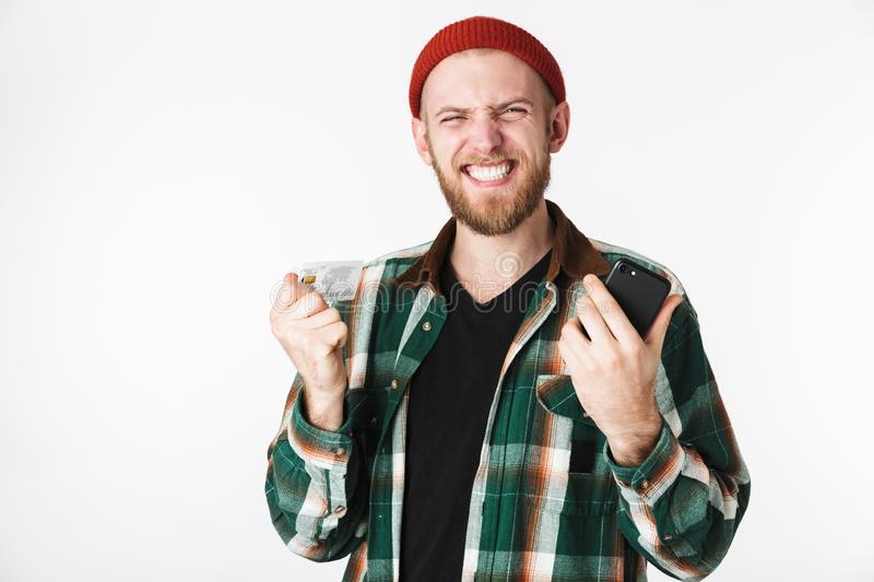 Portrait of pleased bearded guy wearing hat and plaid shirt smiling, while standing isolated over white background royalty free stock images