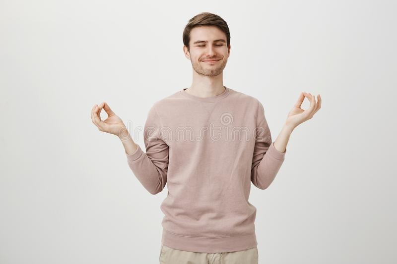 Portrait of pleased and calm young man with satisfied smile standing in yoga pose, spreading hands with zen sign and. Closed eyes, over gray background. Tired stock photo