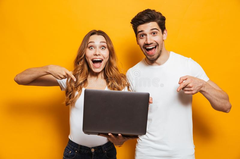 Portrait of pleased positive man and woman holding and pointing stock image