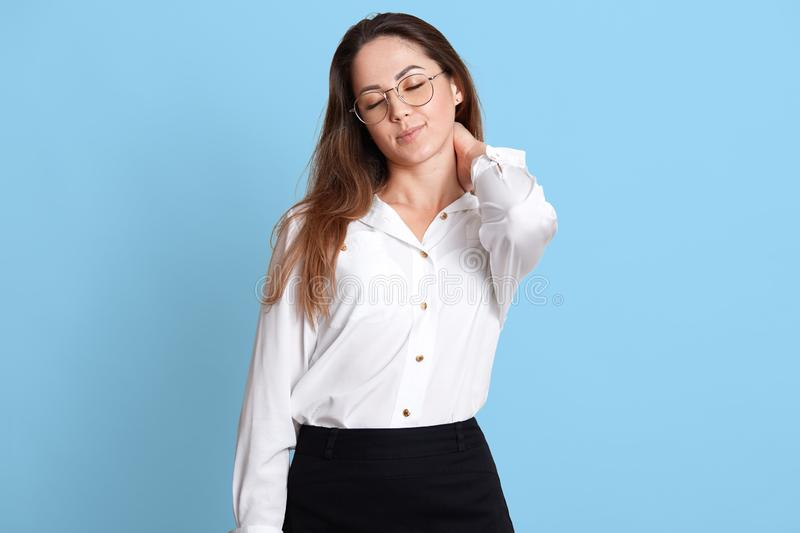 Portrait of pleased smiling young businesswoman in glasses, isolated over blue background, massages her stiff neck with one hand royalty free stock photography
