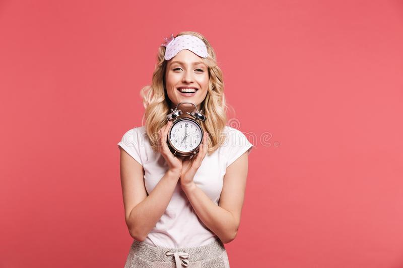 Portrait of pleased young woman 20s wearing sleeping mask holding alarm clock after awakening stock images