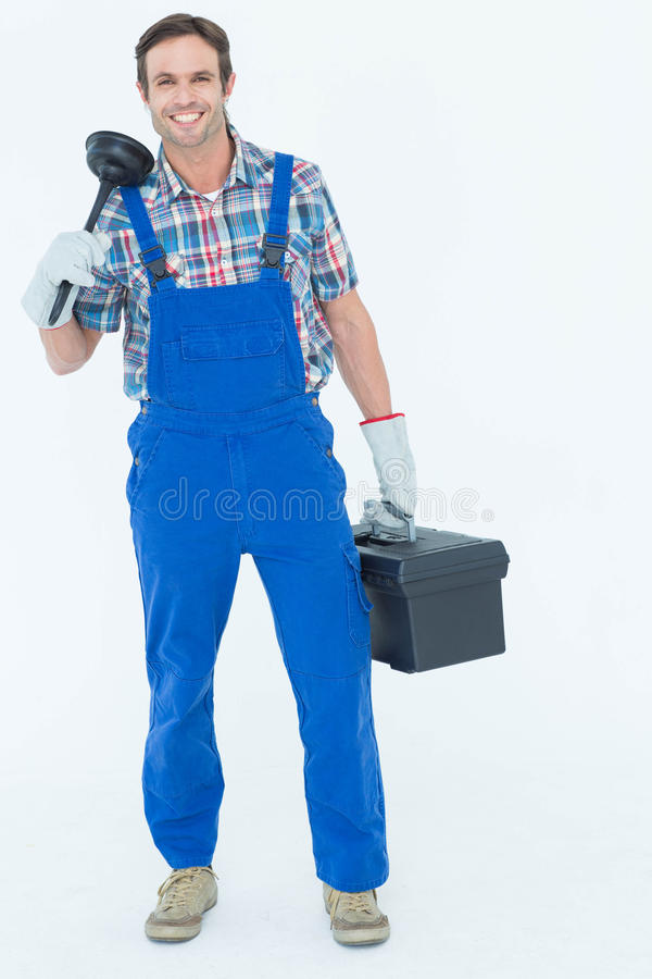 Portrait of plumber holding plunger and tool box. Full length portrait of plumber holding plunger and tool box over white background stock photos