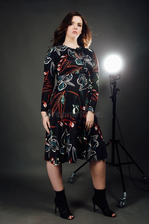 Portrait plus femme de mannequin de taille la grosse sur le fond gris de studio, corps féminin de poids excessif image stock