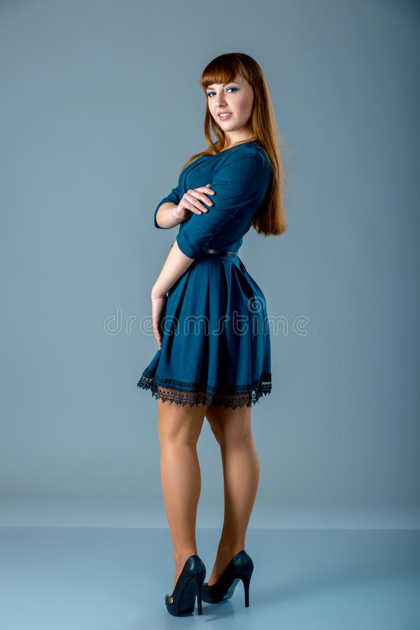 Portrait of a plus size female redhead model posing in blue dress over gray background. Beautiful woman with curvy figure. stock photos