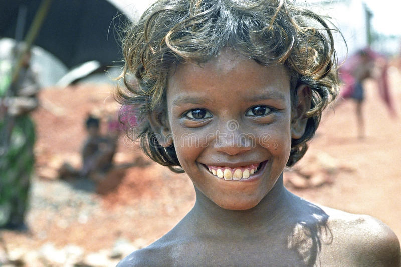 Portrait of poor Bangladeshi boy with radiant face. Bangladesh, capital, city DHAKA: Closeup of a laughing, cheerful child during his work, breaking bricks stock image