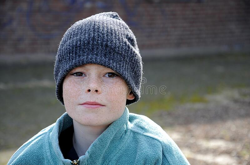 Poor beggar boy with to big clothes royalty free stock photo