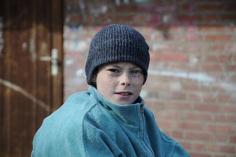 Poor beggar boy with to big clothes royalty free stock photography
