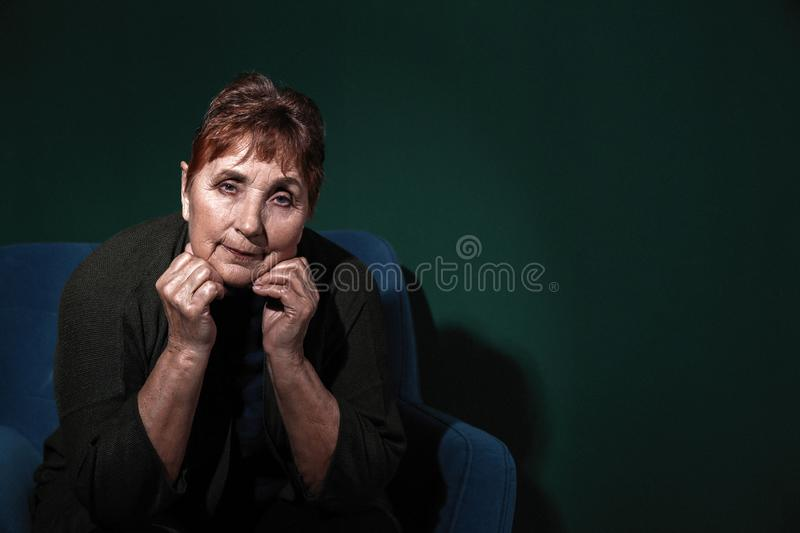 Portrait of poor senior woman on color background stock images