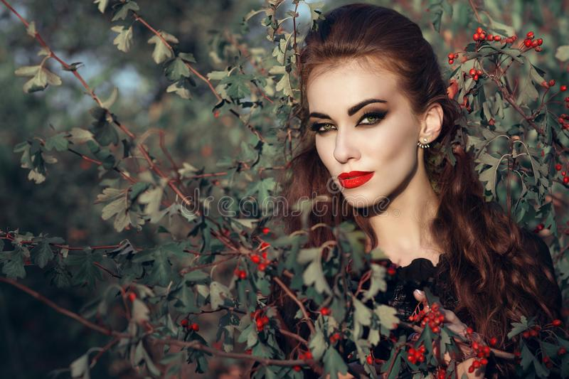 Portrait of posh redheaded woman with provocative make up standing in the berry bush and looking straight with predatory gaze royalty free stock image