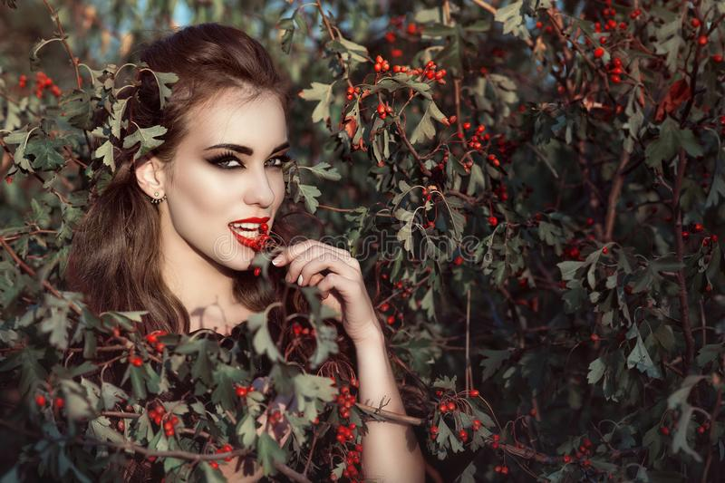 Portrait of posh woman with provocative make up and predatory gaze standing in the berry bush and eating red berries royalty free stock images