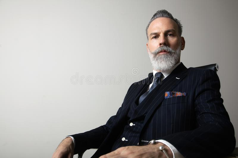 Portrait of positive bearded gentleman wearing trendy suit over empty gray background. Copy Paste space. Studio shot stock photos