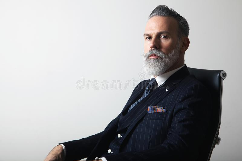 Portrait of positive bearded middle aged gentleman wearing trendy suit over empty gray background. Copy Paste space stock photo