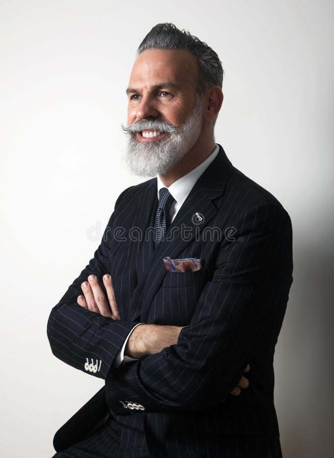 Portrait of positive bearded middle aged gentleman wearing trendy suit over empty gray background. Studio shot. Vertical stock image