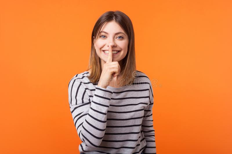 Portrait of positive beautiful woman with brown hair in long sleeve striped shirt. indoor studio shot isolated on orange. Portrait of positive beautiful woman stock images