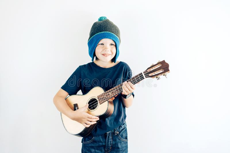 Portrait of a positive boy in casual clothes and hat playing ukulele. Copy space on white background. stock image