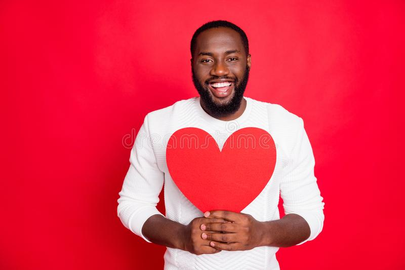 Portrait of positive candid mulatto man hold big paper card heart present for his girlfriend on 14-february wear white. Outfit isolated over, red color royalty free stock photography