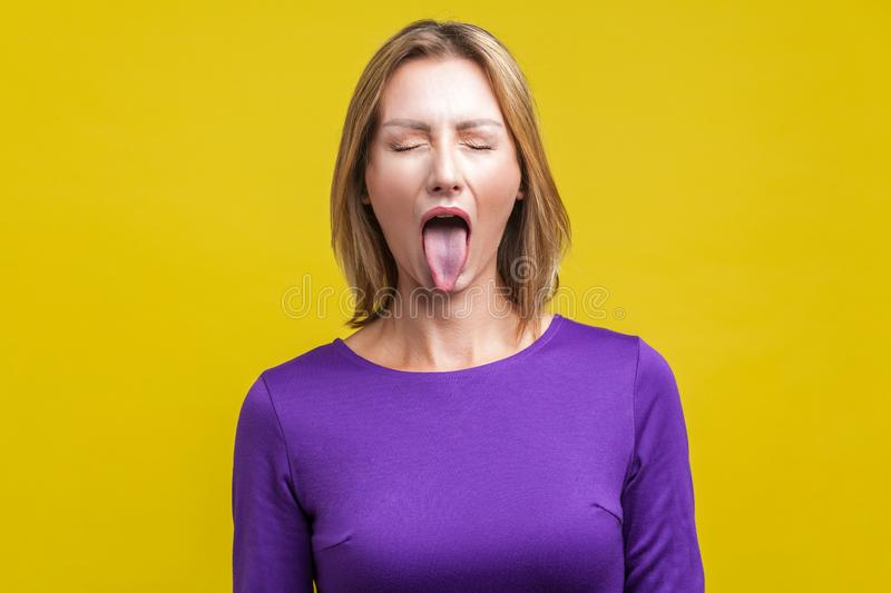 Portrait of positive carefree woman demonstrating tongue. indoor studio shot isolated on yellow background royalty free stock photo