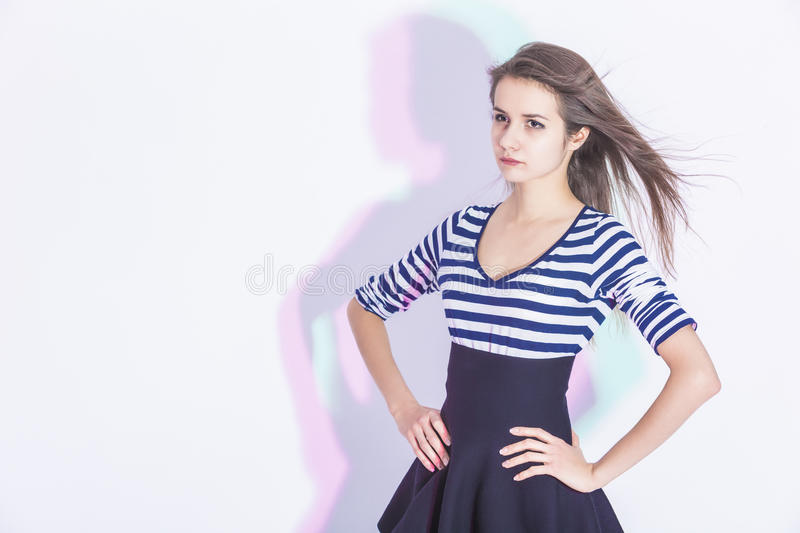 Portrait of Positive Caucasian Brunette Girl In Trendy Striped Blue Dress royalty free stock photography