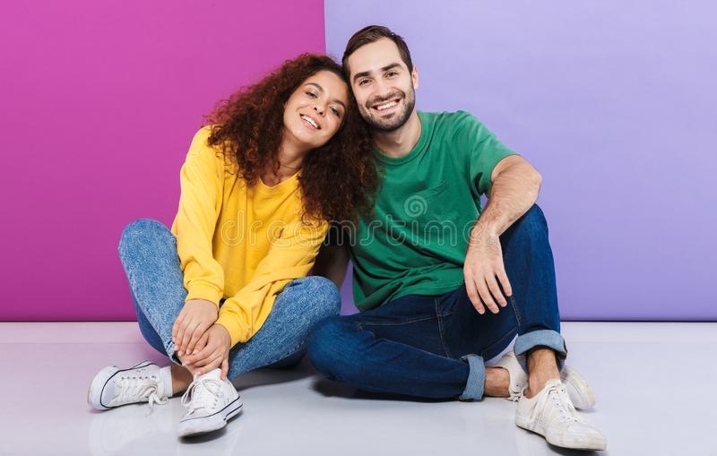 Portrait of positive caucasian couple in colorful clothing smiling and hugging together while sitting on floor stock photo