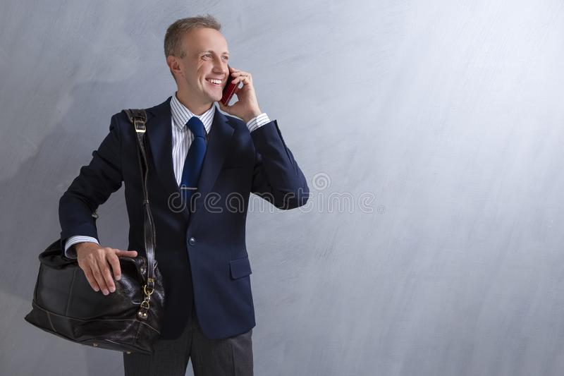 Portrait of Positive Caucasian Male Businessman with Leather Messenger Bag.Talking on Cellphone. Posing Against Grey Wall stock image