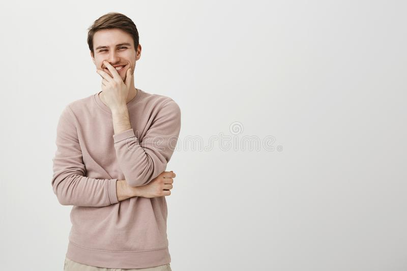 Portrait of positive charming european male covering mouth with hand while laughing and looking aside, standing over. Gray background. Guy is touched with sense stock images