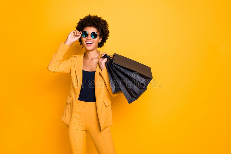 Portrait of positive cheerful afro american girl have fun on free time hold black bags addicted shopper want shop all royalty free stock images