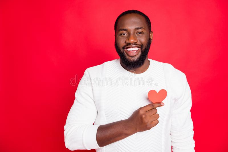 Portrait of positive cheerful candid african man hold small paper card heart show feelings to his sweetheart feel. Portrait of positive cheerful candid african royalty free stock photo