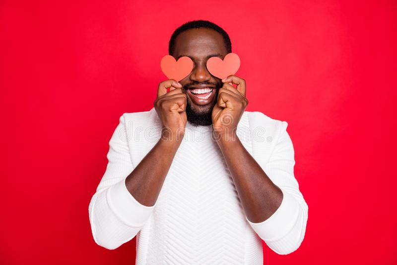 Portrait of positive cheerful expression funky dark skin man hold small paper card heart close eyes want surprise. Girlfriend date 14-february, lover wear white royalty free stock image